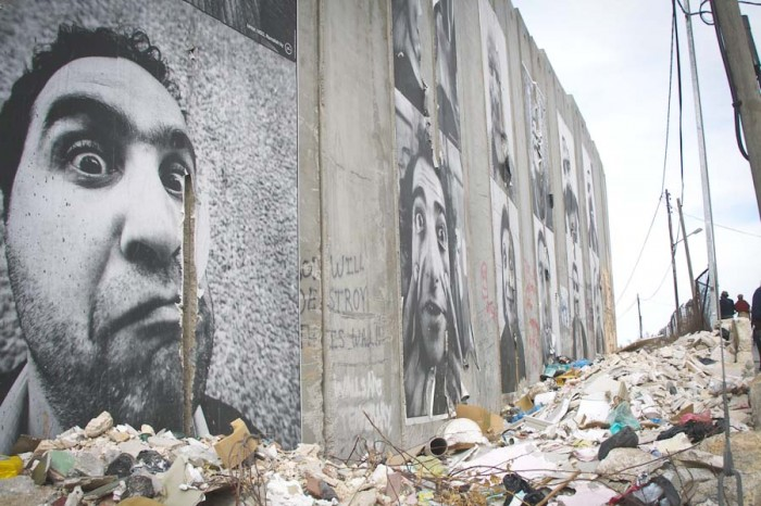 Artwork and graffiti cover the barrier between Jerusalem and the Palestinian West Bank, which was created by the Israeli government following the Second Intifada. Referred to as everything from an apartheid wall to a security fence, ideas about the barrier are reflective of multiple narratives of the conflict. (Photo by Sam Shonkoff)