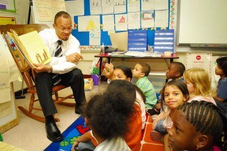 Harold Jones, a paralegal specialist and diversity officer at Navy Medicine Support Command, reads to first-grade students as part of a community volunteer program. (U.S. Navy photo by Mass Communication Specialist 1st Class Bruce Cummins)