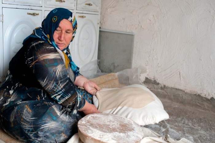 A woman stretches lavash over a pillow in Halabja, in Iraqi Kurdistan. (Photo by Naomi Duguid)