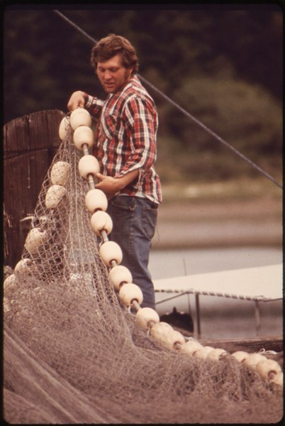 Nick Jerkovich Jr of Gig Harbor works on a seine net for salmon fishing in an archive photo from 1973. (Photo from National Archives/EPA)