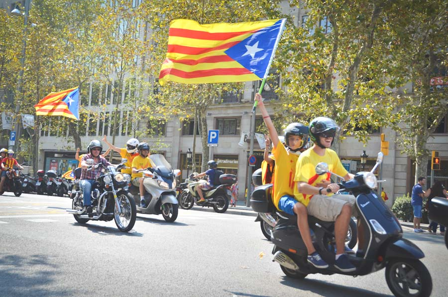 A motorcade of scooters and motorcycles flying Catalonian flags passes through the streets of Barcelona. With a strong economy and a unique language and culture, many Catalonians want to see their region seceed from the rest of Spain. (Photo by Seth Halleran)