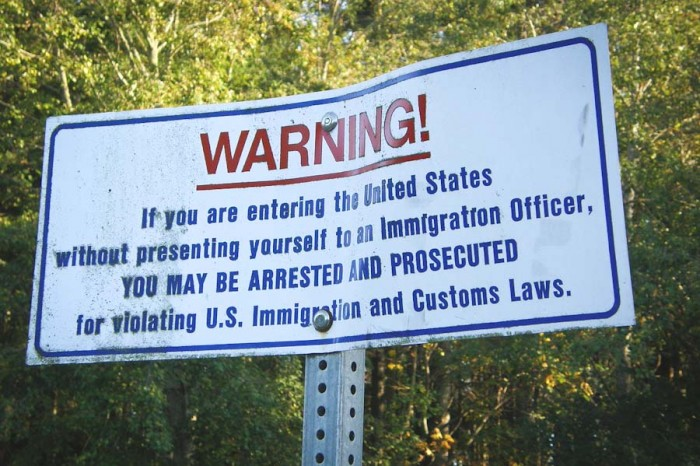 A sign on the U.S.-Canada border at Point Roberts warns undocumented immigrants against crossing illegally. (Photo by Makaristos)