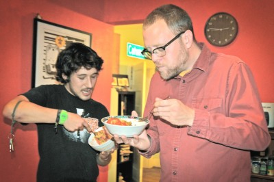 Fred Marshall and Justin Phillips of Beacon Hill share a meal of tomatoes stuffed with pesto and baked tofu, made from ingredients they found unused in dumpsters. (Photo by Rebecca Randall)