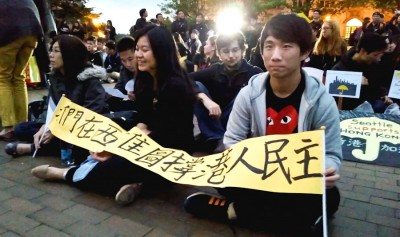 UW students sitting with solidarity signs at a Hong Kong support protest in Red Square Wednesday night. (Photo by Gennie Gebhart)