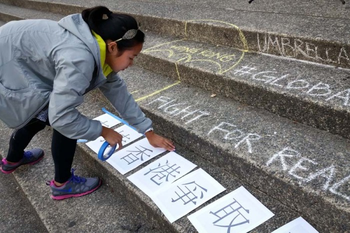 Taping signs to the steps in Red Square. (Photo by Gennie Gebhart)