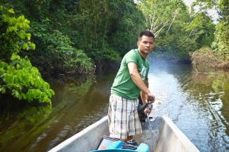 Hugo Lucitante pilots a boat on the Ecuadorian Amazon, on the land of the Cofan people, which is threatened by oil extraction. (Photo courtesy Oil and Water)