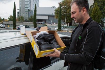 """""""The reason I was late was because I drove to Seattle to pick up boots. Tomorrow I'm going to drive to Olympia to pick up suits for soldiers,"""" said Krasnovsky holding up the shoe box. (Photo by Kseniya Sovenko)"""