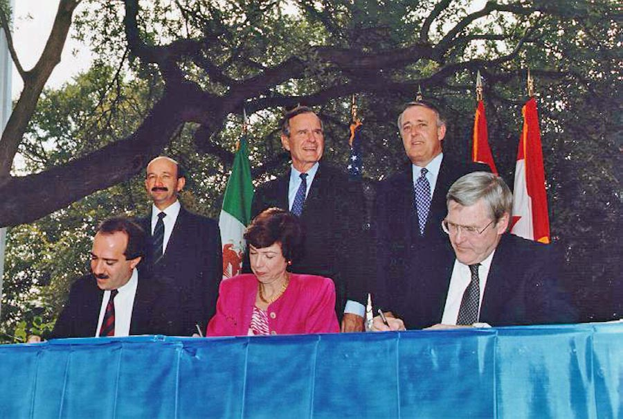 At the NAFTA Initialing Ceremony, in October 1992 , Mexican President Carlos Salinas de Gortari, US President George H. W. Bush, Canadian Prime Minister Brian Mulroney along with trade officials from all three countries. Bill Clinton finalized the negotiations after taking office the next year. (Photo from the George Bush Presidential Library)