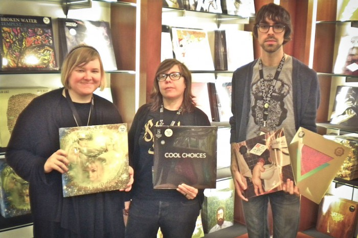 "Sub Pop's Sea-Tac gift shop staff picks, from left: Sarah Cass with ""Dreams in the Rat House"" by Shannon and the Clams; Rachel Rhymes with ""Cool Choices"" by S; Jacob Powers with ""Bakesale"" by Sebadoh and ""Commune"" by Goat. (Photo by Charlie Zaillian)"