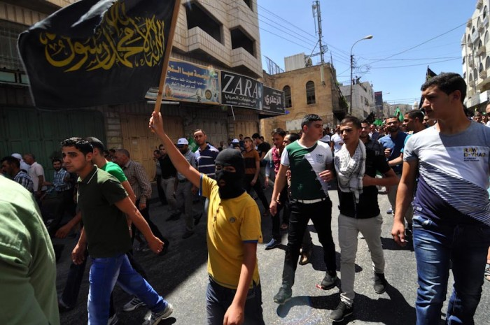 A boy waves the flag of Palestinian Islamic Jihad while marching in an August 1, 2014 protest in Hebron. The march, rallying opposition to the summer Gaza war, later turned violent and area hospitals treated at least 70 protesters for gunshot wounds. (Photo by Tom James)