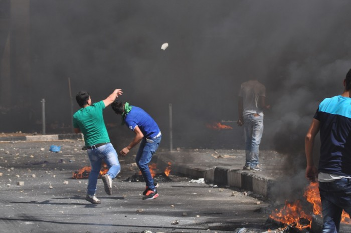 Palestinian youth throwing stones at an Israeli soldiers during a protest in Hebron in August. (Photo by Tom James)
