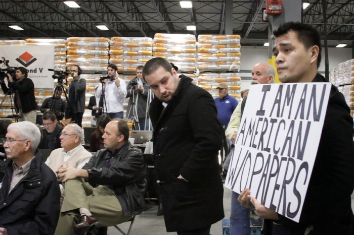 Jose Antonio Vargas flies the undocumented flag at a Mitt Romney presidential campaign rally in Cedar Rapids, Iowa in 2012. (Photo courtesy Apo Anak Productions)