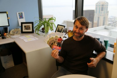 Todd Burley, communications director at Seattle's Office of Housing, holds versions of the Foreclosure Prevention brochures in his office on Oct 17. The brochure is available in 11 languages. (Photo by Senhao Liu)