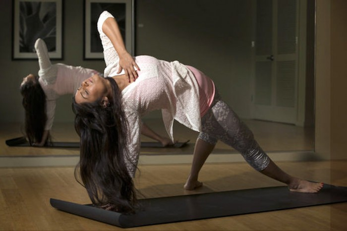 Yoga instructor Sweta Saraogi shows one of her moves in the yoga studio she teaches out of in her condo in Seattle. (Photo by Ellen M. Banner / The Seattle Times)