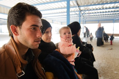 A Syrian family waits at Zaatari Refugee Camp to board a bus back across the border. According to the UNHCR, at least a hundred people return to Syria each day citing frustration with living conditions in the camp, or a desire to reunite with family, despite the risks.(Photo by Alisa Reznick)