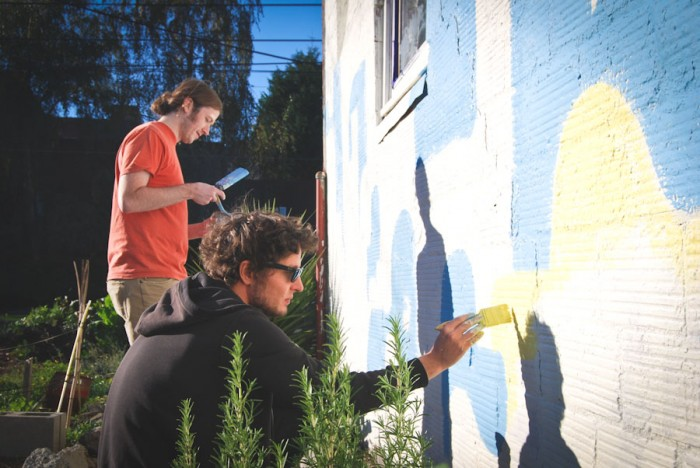 During his visit to Seattle, South African comics artist Jean de Wet (front, with local collaborator James Stanton) is painting a mural on the Cappy's Boxing Gym building in the Central District. (Photo by Ana Sofia Knauf)