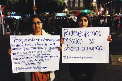 "Fabiola (left) and Michelle, students at the Instituto Tecnologico de Monterrey hold up signs at the Dia de Accion in Mexico City that read ""For this great humanity has said 'enough' and has started to move forward. And their march, the march of giants, cannot stop, will not stop until they have conquered their true independence, for which many have already died, and not uselessly."" Ernesto ""Che"" Guevara and ""Let's reinvent Mexico, it's now or never."" (Photo by Gloria Mayne Devó)"