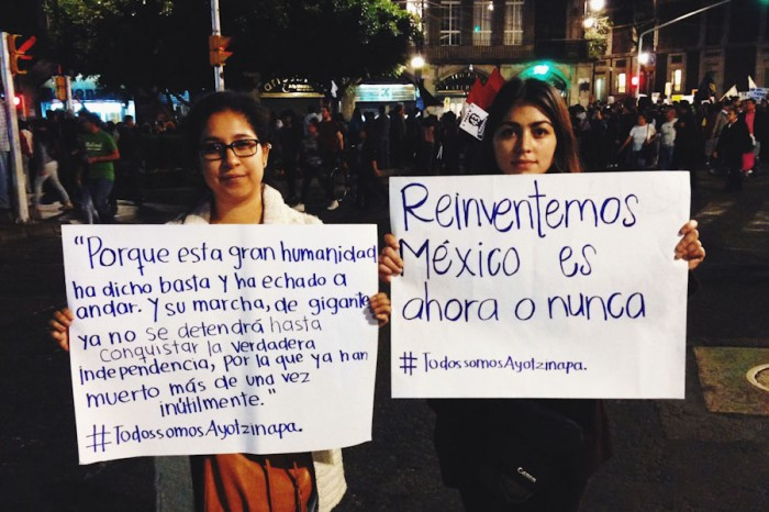 "Fabiola (left) and Michelle, students from Monterrey hold up signs at the Dia de Accion in Mexico City that read ""For this great humanity has said 'enough' and has started to move forward. And their march, the march of giants, cannot stop, will not stop until they have conquered their true independence, for which many have already died, and not uselessly."" Ernesto ""Che"" Guevara and ""Let's reinvent Mexico, it's now or never."" (Photo by Gloria Mayne Devó)"