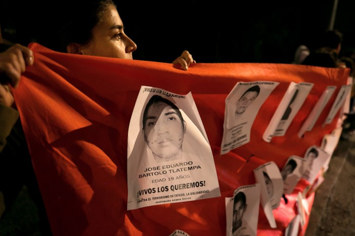 A student at the National Autonomous University of Mexico holds up a banner with the faces of the 43 missing students from Ayotzinapa. (Photo from Flickr by Montecruz Foto)