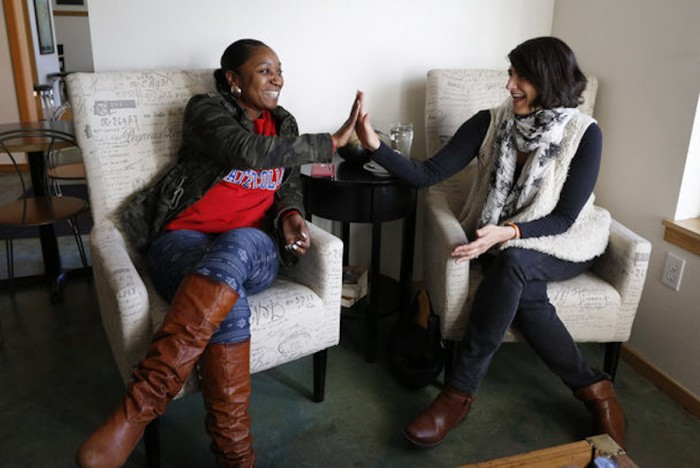 Patrice Thomas, left, and Maia Segura discuss community development and diversity at Kaffa Coffee & Wine Bar on Rainier Avenue South in Seattle. (Photo by Mark Harrison / The Seattle Times)