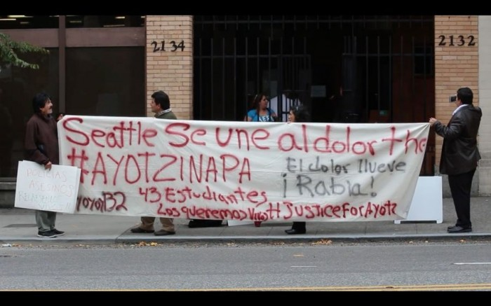 Protesters in front of the Consulate General of Mexico in Seattle demonstrate solidarity alongside the 43 missing students in Mexico and their loved ones. (Photo from Sarahy Sigie's documentary video, Seattle Is With Ayotzinapa's Pain)