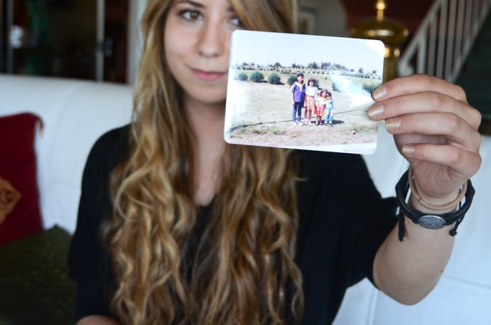 Reham Hamoui holds up a photo of her and her siblings before the family fled Syria in 1992. (Photo by Alisa Reznick)
