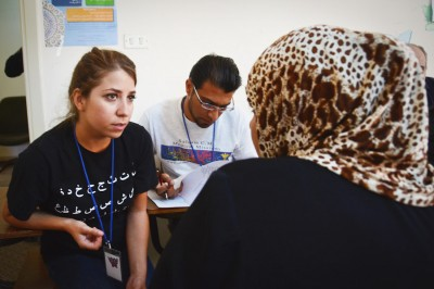 Reham Hamoui interprets for a Syrian refugee at a pop-up clinic held during the Seattle-based Salaam Cultural Museum's week-long aid mission in Jordan in September.