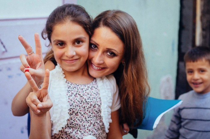 Oula Abdulhamid-Alrifai poses with a Syrian refugee child last year in the Turkish border town of Gaziantep, where she was documenting the lives of young refugees in Turkey. (Courtesy photo)