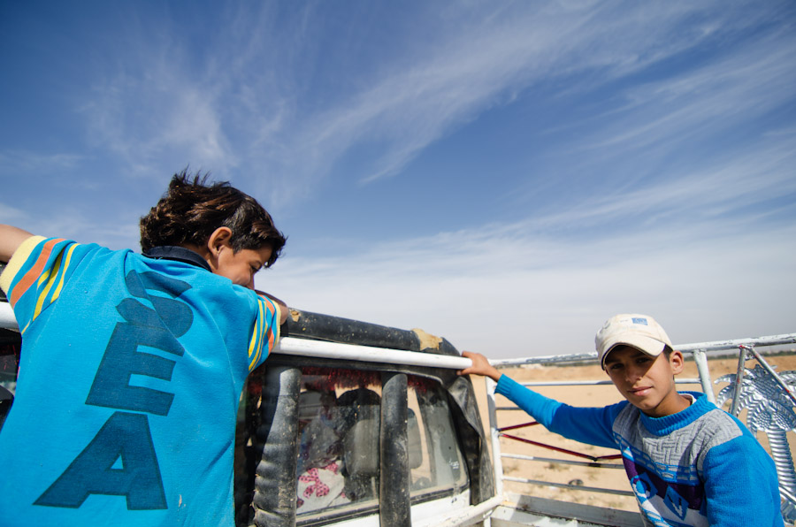Syrian children at Jordan's Zaatari Refugee Camp ride on the back of a Jordanian's pickup truck.  Zaatari offers kindergarten and elementary schooling for the refugees, but overcrowded classrooms and labor needs at home keep many young refugees from attending. (Photo by Alisa Reznick)