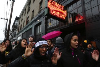 "Chanting ""hands up, don't shoot,"" protesters briefly blocked the entrance to the Comet Tavern on Black Friday, saying that the business owners discriminated against East African youth. (Photo by Alan Berner / The Seattle Times)"