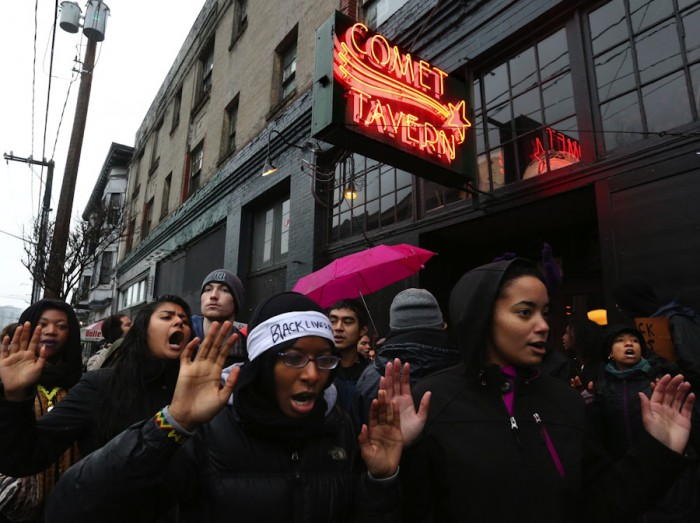 """Chanting """"hands up, don't shoot,"""" protesters briefly blocked the entrance to the Comet Tavern on Black Friday, saying that the business owners discriminated against East African youth. (Photo by Alan Berner / The Seattle Times)"""