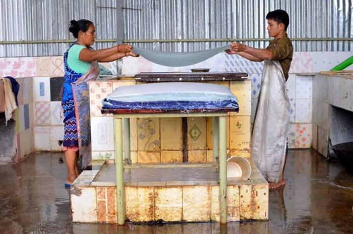 Two ElRhino employees lift wet paper out of a vat. (Upaya courtesy photo)