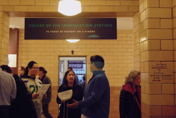 "Cassie Chinn, deputy director of the Wing Luke Museum, center, talks with visitors during the opening night of ""Voices of the Immigration Station."" (Photo by Ana Sofia Knauf)"