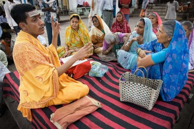 A priest in Varanasi leads women in a class on Hindu scripture. Traditionally in India women do more meditation and chanting, while the physical aspects of yoga are reserved for men. (Photo by Jorge Royan)