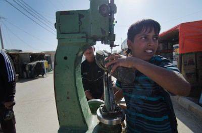 An 12-year-old Syrian boy sews reinforcement stitches on donated shoes at his parent's storefront in the Zaatari Camp's main market area. In lieu of going to one of the schools offered at the camp, many children end up working for their parents or in other shops to bring in extra money for the family. (Photo by Alisa Reznick)