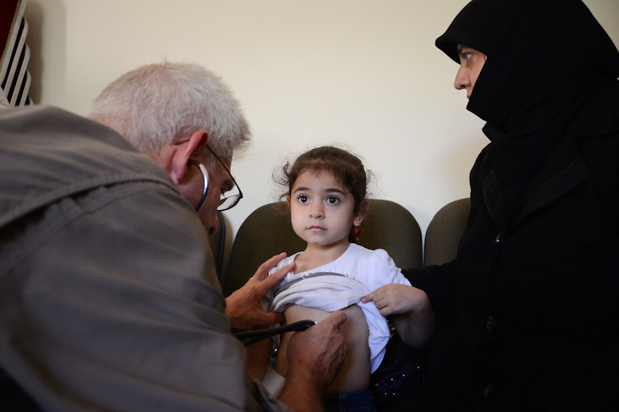 A volunteer doctor working with the Salaam Cultural Museum examines a Syrian refugee child. (Photo by Alisa Reznick)