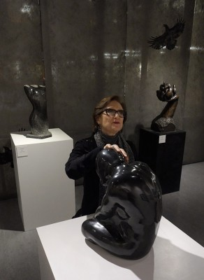 "Camille Jassny, who is blind, touches ""Quiet Moment"" , a basalt sculpture created by Sabah Al-Dhaher. In the background at left is Sabah's ""Female Torso"" a basalt piece and to the right, background is Sabah's bronze piece ""Beginning."" These are part of a current show titled Please Touch which is showing at the Edmonds Community College library gallery. (Photo by Jim Ballard)"