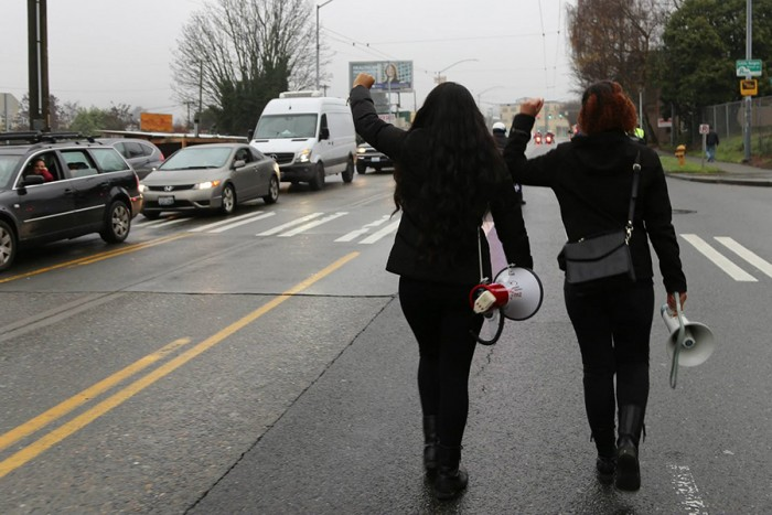 Aretha Basu and Harmony Wright marching along Martin Luther King, Jr. Way during their Jan. 10th protest. (Photo by Naomi Ishisaka)