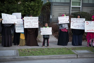 Signs carried by Somali American protesters alluded to complaints about policy at ReWA beyond just the cartoons. (Photo by Alex Garland)