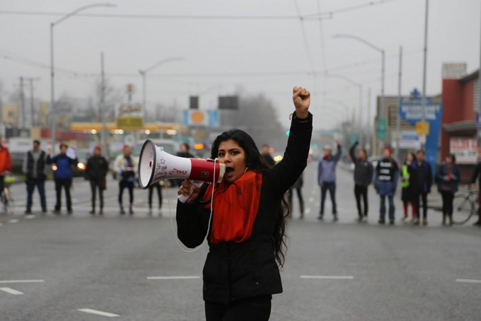 Aretha Basu leads a chant on Rainier Avenue South and Dearborn Street during their Jan. 10 police accountability protest. (Photo by Naomi Ishisaka)