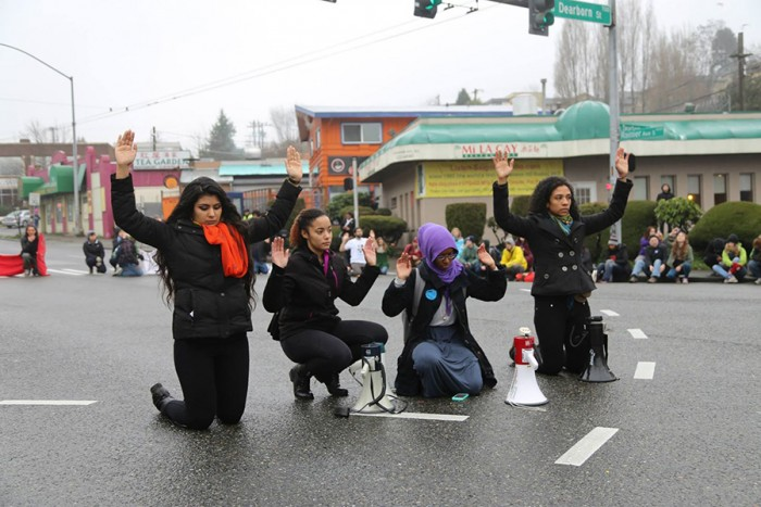 "Basu, Wright, Ahmed and Canez lead the ""Hands up! Don't shoot!"" chant on Jan. 10 with protesters gathered round on the corner of Rainier Avenue South and Dearborn Street. (Photo by Naomi Ishisaka)"