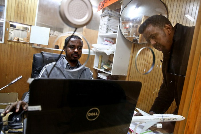 Adem Issa, an employee at Tawakal Express in SeaTac, works on a money transfer for Mohmed Egal, who was sending money to Nairobi, Kenya to help with his brother's education. (Photo by Erika Schultz / The Seattle Times)
