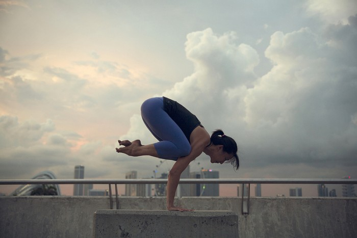 A woman practices the crow yoga pose