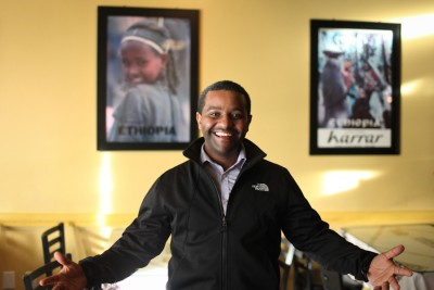 Amen Gibreab in front of vintage posters advertising tourism to Ethiopia. (Photo by Alex Stonehill)