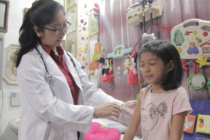 A doctor vaccinates a young girl. (Photo by Gabriel Pagcaliwaga for Sanofi Pasteur, via Flickr)