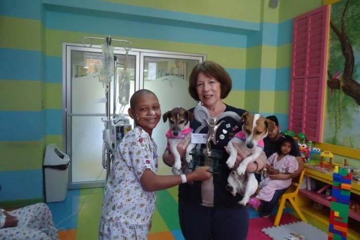 A volunteer brings therapy dogs to a pediatric cancer center in Guatemala. Photo by Fundación Ayúdame a Vivir via Facebook.