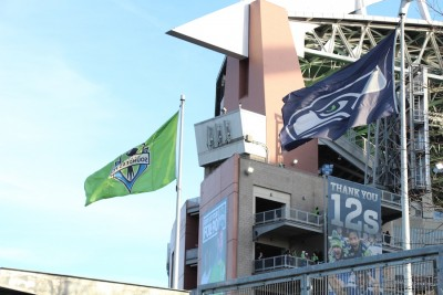 The Sounders FC flag waves alongside the Seattle Seahawks flag on the north side of Century Link Field (Photo by Justice Magraw)