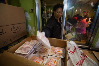 """Calise Wiggins, a volunteer at Rainier Valley Food Bank, grabs some chicken drumsticks for a guest. The meat distribution was reorganized, thanks to a Japanese corporate philosophy called Kaizen, which means """"good change."""" (Ellen M. Banner/The Seattle Times)"""