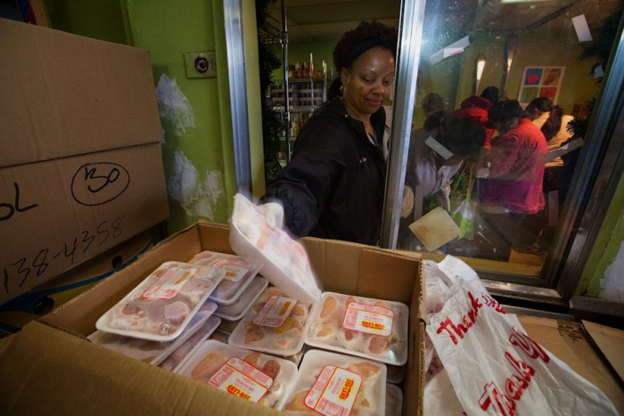 "Calise Wiggins, a volunteer at Rainier Valley Food Bank, grabs some chicken drumsticks for a guest. The meat distribution was reorganized, thanks to a Japanese corporate philosophy called Kaizen, which means ""good change."" (Ellen M. Banner/The Seattle Times)"