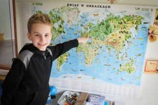 Fourth grader Arthur Gwozdz of Newcastle points at his parents' native Poland on a map in his family's living room. (Photo by Kyle Haddad-Fonda)